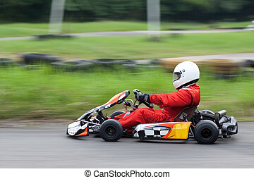Panning shot of go kart racer - A go kart racer zooms past...