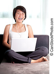 Young Asian executive laughs while chatting online/watching...