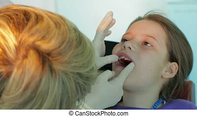 Orthodontist Trying On Plate In Girl's Mouth - Shot of an...