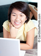 Young Asian girl browsing the net on couch