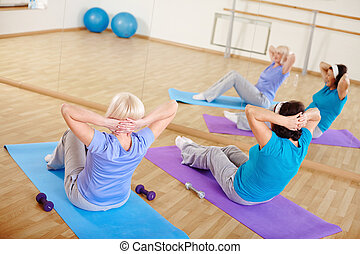 Sit-ups - Mature females doing sit-ups on mats in sport gym