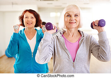 Happy workout - Two sporty females doing exercising with...