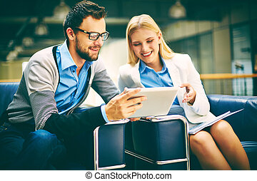 Teamwork - Two business people using touchpad during...