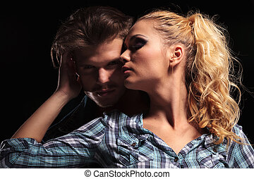 Blonde woman looking away and embracing her boyfriend -...