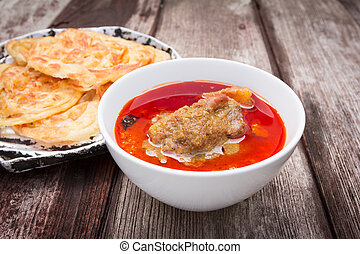 roti canai with spicy curry on old wood background