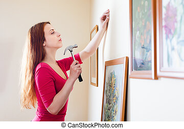 girl in red hanging  pictures in frames