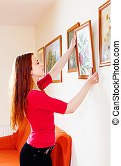 woman in red hanging the  pictures