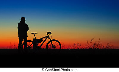 Bicycler silhouette on sunset