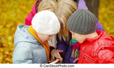 Share It All - Close up of four kids using one device at...