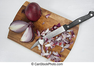 Red onion on wooden board with knife