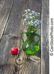 Forget-me-not flowers in vase and apple on wooden background