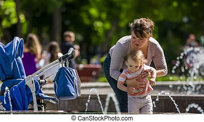 Mother Puts Baby Into Stroller In the Park - Slow motion-...