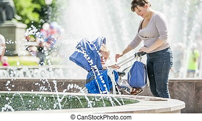 Mother And Baby Watching Fountains In The Park - Slow motion...