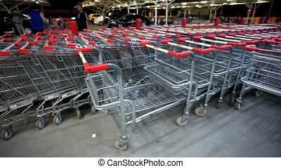 Many empty shopping carts in a row at parking of supermarket on Koh Samui
