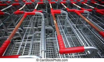 Many empty shopping carts in a row at parking of supermarket...