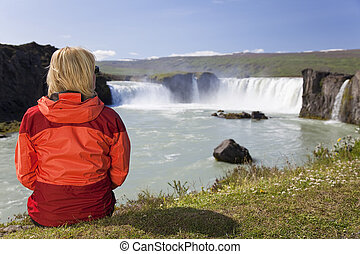 Woman Sitting At Godafoss Waterfall In Iceland - A young...