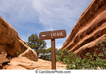 trail sign between sandstone cliffs - rusty back-country...