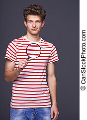 Man holding magnifying glass - Stylish young man holding...