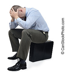 Business problems - a businessman with head in hands sat on...
