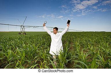Satisfied agronomist standing with tablet and magnifier in...