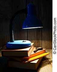 The fixture, books and a magnifier On a wooden background