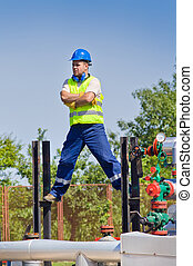 Oil worker standing in dangerous pose on plant