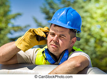 Oil worker - Tired worker with walkie talkie and safety...