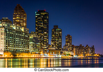 The Manhattan Skyline and the East River at night, seen from...