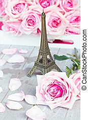 pink roses with eiffel tour on table - two fresh blooming...