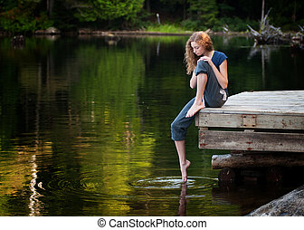 girl sitting by a lake