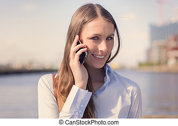 Attractive woman taking a call on her mobile phone standing...