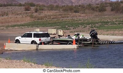 Boat being put back in a lake - A shot of a car backing up,...