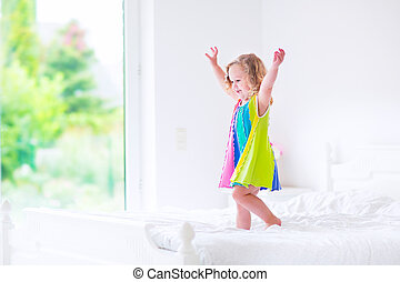 Little girl jumping on a bed - Cute little curly toddler...