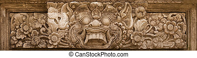 Horrible mythical monster face. Stone relief from Indonesia,...