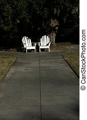 Two Chairs - Two white Adirondack Chairs sit empty at the...
