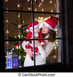 Mother and baby dressed as Santa at a window on Christmas