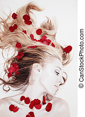 Woman with rose petals in her hair