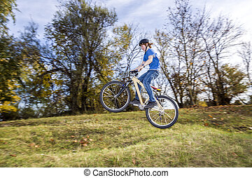boy jumps over a ramp with his dirt bike - teenage boy jumps...