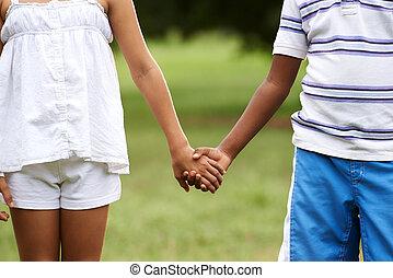 Children love black boy white girl holding hands -...