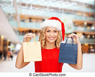 woman in santa helper hat with shopping bags - sale, gifts,...