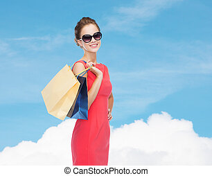 smiling elegant woman in dress with shopping bags -...