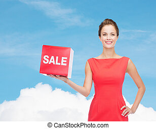 smiling young woman in dress with red sale sign - shopping,...