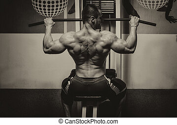 Young Bodybuilder Doing Heavy Weight Exercise For Back -...