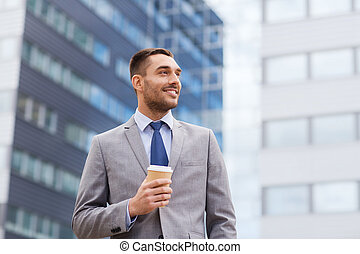 young smiling businessman with paper cup outdoors -...