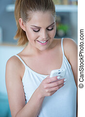 Young Woman Looking Down at Cell Phone - Young Woman Wearing...