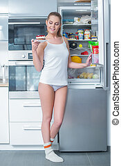Pretty young woman eyeing a slice of cake she has just...