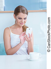 Smiling young woman sending an sms text messasge on her...