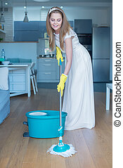 Woman Wearing Wedding Gown Mopping Floor - Woman Wearing...