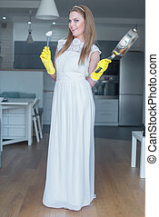 Woman Wearing Wedding Gown Holding Pan in Kitchen - Woman...