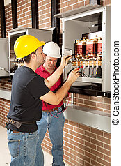 Industrial Maintenance Work - Workers testing the voltage of...